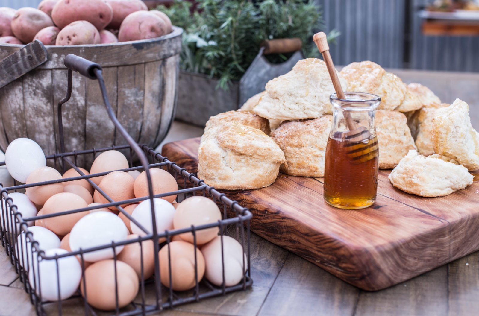biscuits with jar of honey, basket of eggs, and basket of potatoes